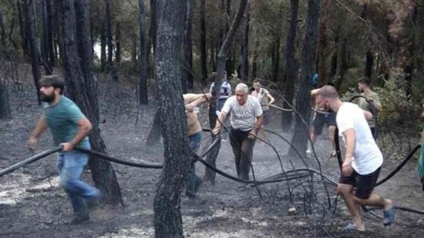 Foto - İzmir'in Gaziemir ilçesi Sarnıç semti Atatürk Mahallesi'ndeki yangını söndürme çalışmalarına aralarında çocukların da bulunduğu onlarca vatandaş da destek verdi. Bazı vatandaşlar ağaç dallarıyla müdahale ederken, bazı vatandaşların yangın söndürme hortumu taşıdığı görüldü.