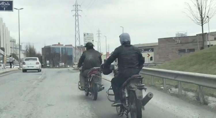Kasksız motosikletli, yakıtı biten başka bir motosikleti iple çekti